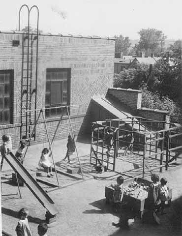 Black and white photograph of children playing on the playground of St. Paul's Neighborhood House in 1937.