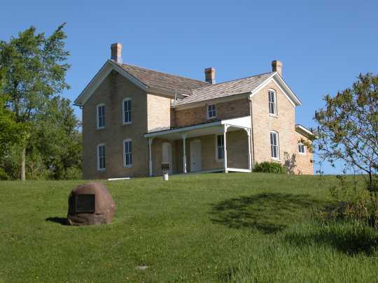 Image depicting the 1876 Chaska brick Wendelin and Julianna Grimm house, showing 1924 Grimm alfalfa marker in foreground, 2004.