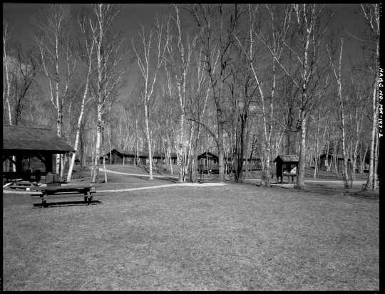 Southwest section of Civilian Conservation Corps Camp Rabideau F-50, looking northeast, with (left to right) picnic shelter, barracks, forest service officer's quarters, and hospital. Photo by Jerry Mathiason, 1994. From box 1 (144.G.8.4F) of Historic American Buildings Survey records related to Minnesota structures, 1882-2001, 1883. Manuscripts Collection, Minnesota Historical Society, St. Paul.