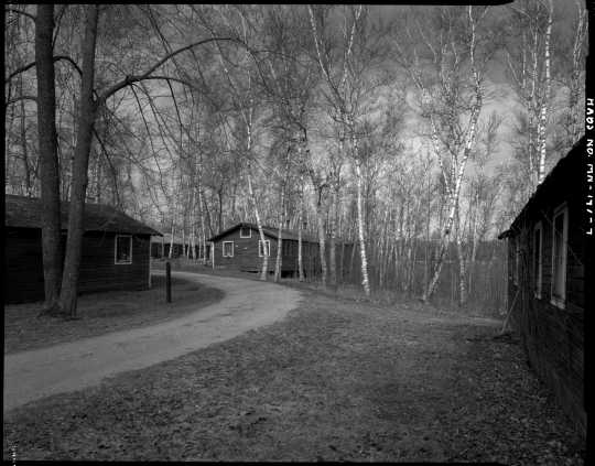 Northwest section of CCC Camp Rabideau F-50, looking southwest, with (left to right) barracks, education building, barracks, and recreation hall. Photo by Jerry Mathiason, 1994. From box 1 (144.G.8.4F) of Historic American Buildings Survey records related to Minnesota structures, 1882-2001, 1883. Manuscripts Collection, Minnesota Historical Society, St. Paul.