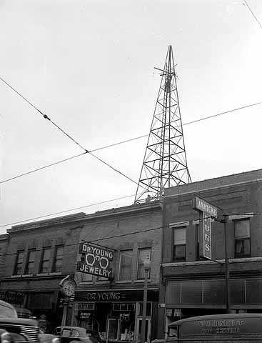 Black and white photograph of a WDGY radio tower, 1947. Photographed by the Minneapolis Star Journal.  The optometry shop of Dr. George Young, the founder of WDGY, is visible below the tower.