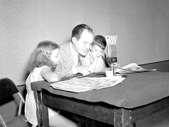 Black and white photograph of Hubert Humphrey reading comics on the radio, August 1946.