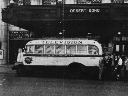 Black and white photograph of a Twin City Television Lab mobile unit in front of the Lyceum Theater and the Lab's main entrance, c.1948.