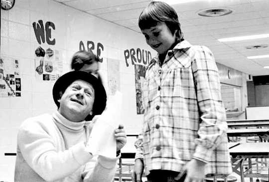Black and white photograph of television character Roundhouse Rodney (played by Lynn Dwyer on WTCN) signing an autograph for a young fan, c.1961.