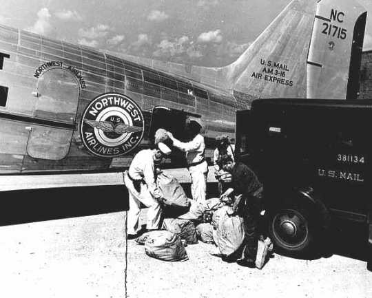 Black and white photograph of an air mail being loaded onto a Northwest Airlines plane, c.1940.