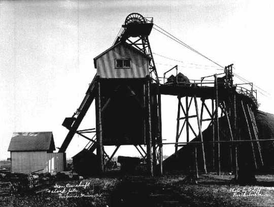 Black and white photograph of an iron ore shaft and stock pile in Virginia, Minnesota, 1915.