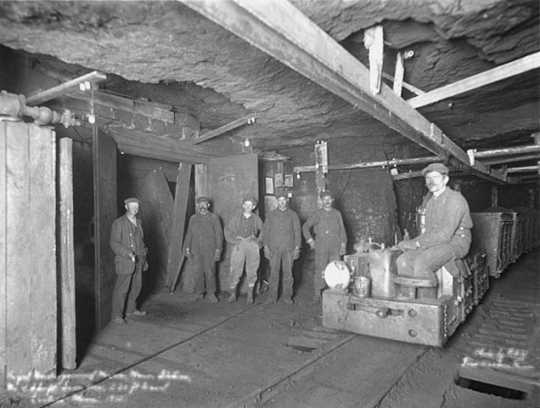 Black and white photograph of miners inside the Fayal mine in Eveleth, 1915. Photographed by William F. Roleff.