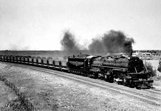 Black and white photograph of a ellowstone locomotive pulling a string of jennies near Duluth, 1940.