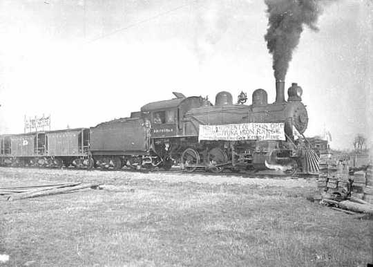Black and white photograph of a train carrying first shipment of iron ore from the Kennedy Mine on the Cuyuna Iron Range, 1911.