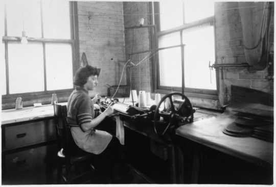 Black and white photograph of an employee knitting a sock to cover an amputated limb, Winkley Artificial Limb Company, Minneapolis, 1937.
