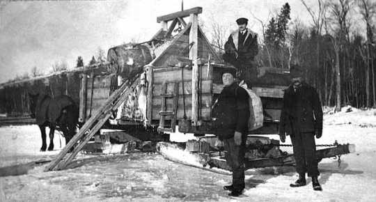 Photograph of Frank Higgins (at left) with two unidentified men near a water wagon c.1920.