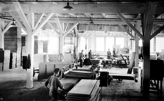 Black and white photograph showing the interior of a lumber mill, ca. 1915.
