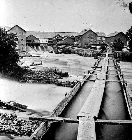 Black and white photograph of a cluster of Minneapolis sawmills, c.1865.