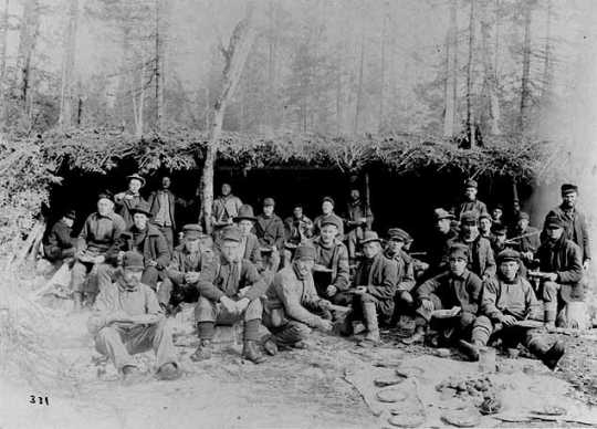 Black and white photograph of a Lumber crew eating outdoors, ca. 1900. Photograph by A.A. Swan.