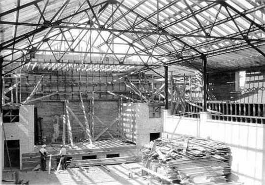 Black and white photograph of Deerwood Auditorium interior under construction, c. 1936.