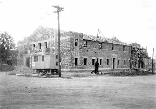 Black and white photograph of the exterior of Deerwood Auditorium exterior under construction, c.1936.