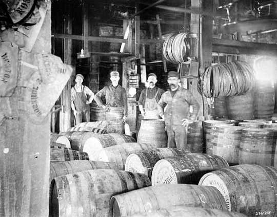 Black and white photograph of M. A. Company workers constructing vinegar barrels, c.1912.