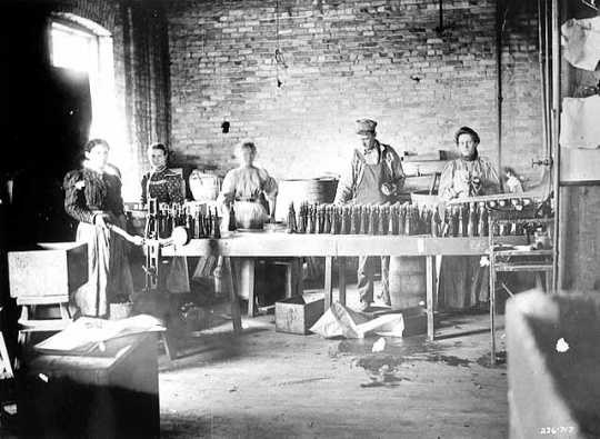 Black and white photograph of M. A. Gedney Company workers bottling product, c.1912.