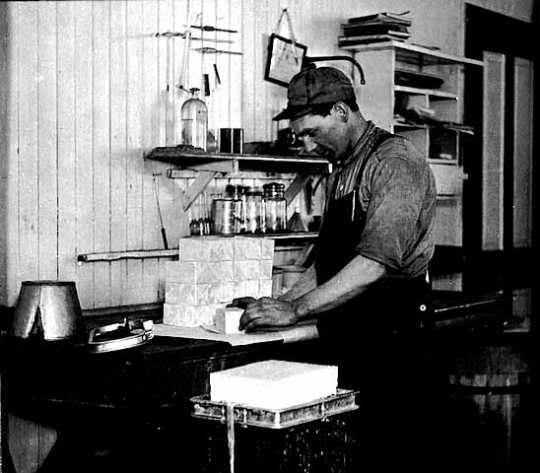 Black and white photograph of a worker packing butter at a creamery in Hawley, c. 1917.