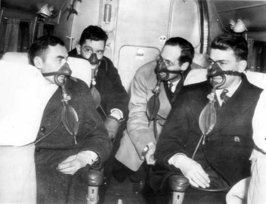Black and white photograph of passengers with oxygen masks on Northwest Airlines plane, c.1940.