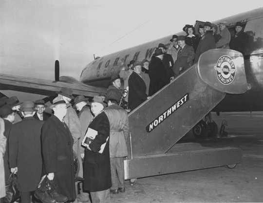 Black and white photograph of passengers boarding a Northwest Airlines plane, c.1946. Photographed by Philip C. Dittes.