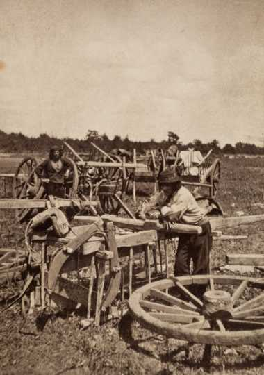 Black and white photograph of two men, probably Métis, preparing a Red River cart train at Pembina, 1856.