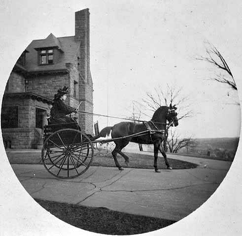 Black and white photograph of Rachael Hill in a horse-drawn buggy at the James J. Hill House, 240 Summit, St. Paul, 1898.