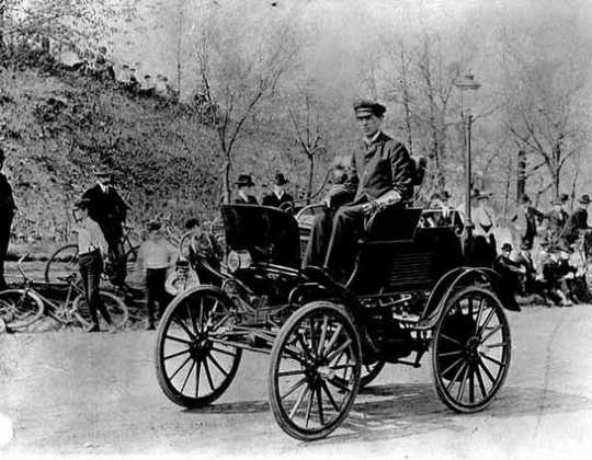 Black and white photograph of Swan Turnblad, ca. 1900 driving his Waverly automobile—the first commercially available car owned by a Minnesotan.
