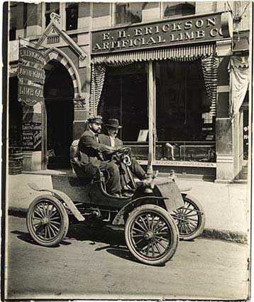 Black and white photograph of Michael Dowling and a passenger in a car in front of the E.H. Erickson Artificial Limb Company, c.1905.