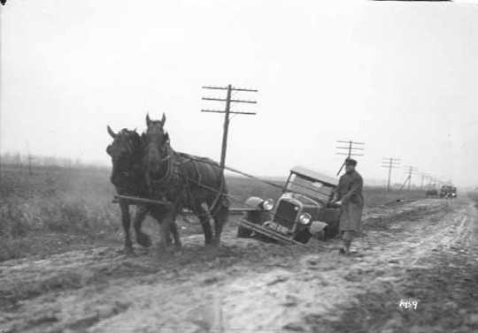 Horses pulling a car out of mud on a dirt road
