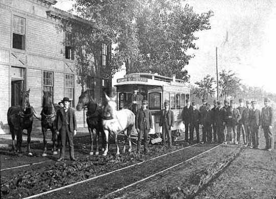 Black and white photograph of a horse-drawn streetcar in Minneapolis; sign reads Sixth Street, Monroe Street and Eighth Avenue, c.1885. This photograph shows a second team of horses ready to relieve the team on the horsecar.