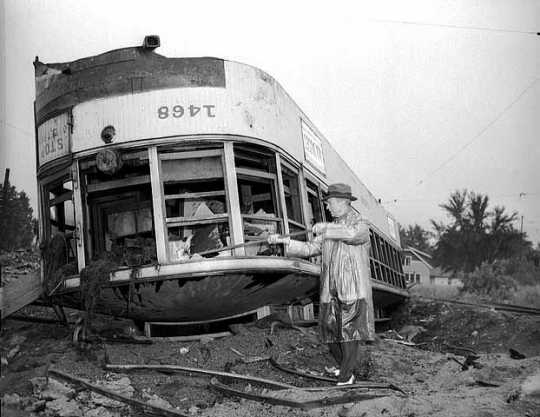 Black and white photograph of Minneapolis farewell to streetcars. TCRT Chairman, Fred A. Ossanna, smashes the window of an electric streetcar following the implementation of motor buses in Minneapolis, 1954.