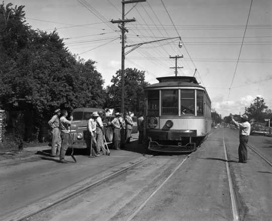 Black and white photograph of the last streetcar to run on France between Forty-Forth Street and Fifty-Forth Street passes the work crew that is about to tear up the track, August 10, 1952.