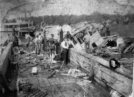 Black and white photograph of National Guardsmen searching for survivors in the wreckage of the Sea Wing, 1890. The men at left are standing in the Sea Wing's attached barge, Jim Grant. The Lake City steamer Ethel Howard is in the background.