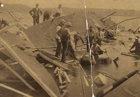 Black and white photograph of rescue workers searching for bodies in the wreckage of the Sea Wing, 1890.