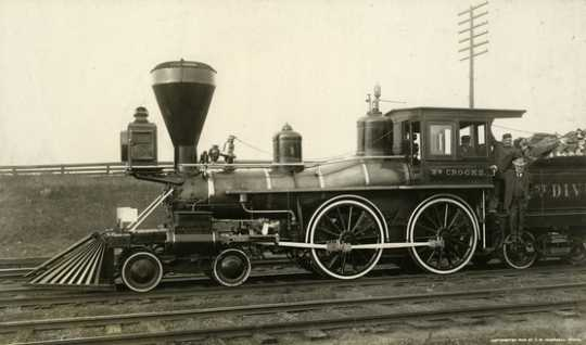 Black and white photograph of James J. Hill with two engineers on the William Crooks train engine, 1908. Photograph by T.W. Ingersoll.