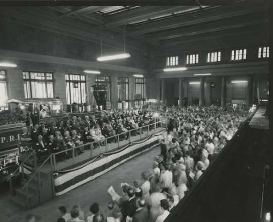 Black and white photograph of speaker's stand and crowd at the 100th anniversary celebration of the Great Northern Railway at St. Paul's Union Depot, 1962.