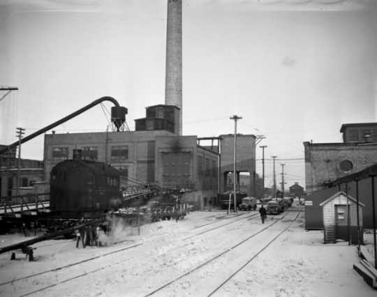 Black and white photograph of the Como Shops complex of the Northern Pacific Railway, located just south of Como Park in the St. Paul Midway, 1948. A railroad crane is parked next to the powerhouse building.