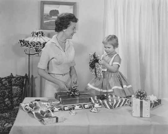 A mother and her daughter wrap gifts with Sasheen ribbon in this ca. 1955 advertisement for 3M.