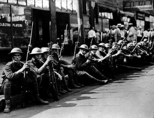 Black and white photograph of the National Guard seated along street curb, Minneapolis, 1934.