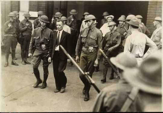 Black and white photograph of Vincent R. Dunne, strike committee member, arrested and held at the provost guard stockade at the State Fair grounds, 1934.