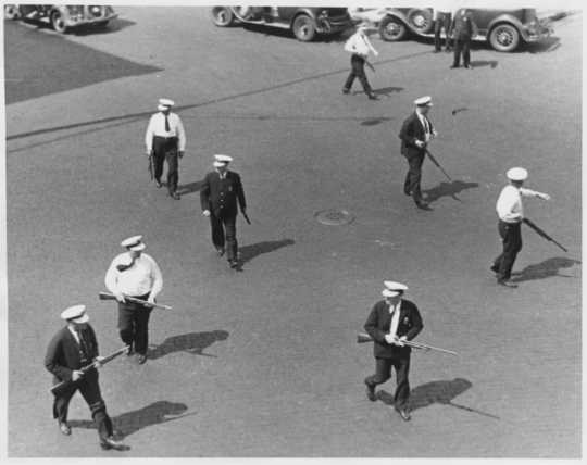 Black and white photograph of police carrying shotguns during the truck drivers' strike, 1934.