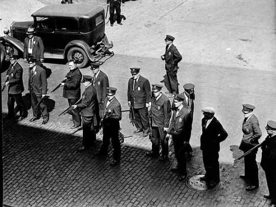 Black and white photograph of police with guns on a Minneapolis street during the strike, 1934.