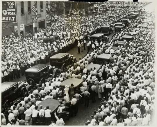 Black and white photograph of the funeral of Henry Ness, a striker killed during the strike, in front of strike headquarters at 215 South Eighth Street, Minneapolis, 1934.