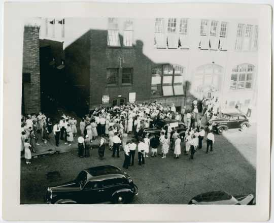 Crowd demonstrating in front of the Minneapolis sewing project
