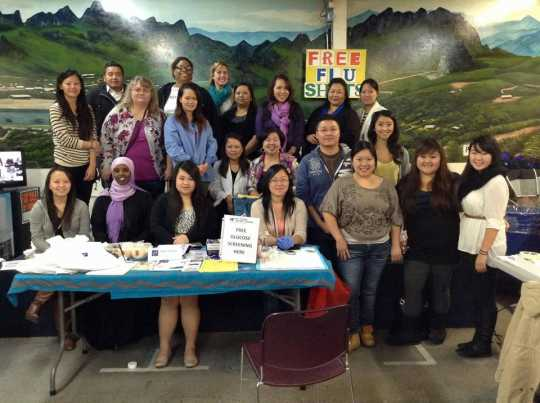 Color image of participants in the Operation Free Flu Shot program gather for a group photograph at the Hmong New Year celebration in St. Paul's RiverCentre on November 24, 2012.