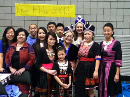Color image of participants in the Operation Free Flu Shot program gather for a group photograph at Hmong Village in St. Paul on October 27, 2013.