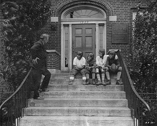 Black and white photograph of a boys wearing football helmets on the front steps of the Northeast Neighborhood House, 1927.
