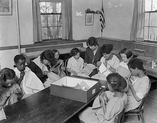 Black and white photograph of members of a sewing class at St. Paul's Neighborhood House, c.1920.