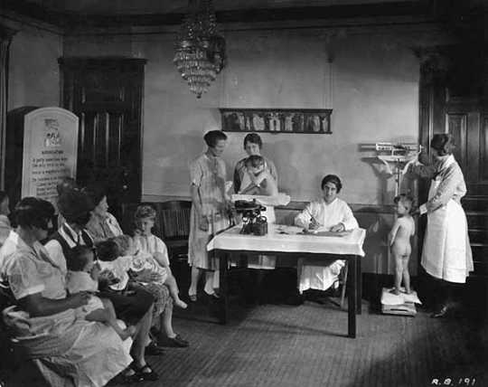 Black and white photograph of children being weighed at the Emanuel Cohen Center Clinic in Minneapolis, c.1925.